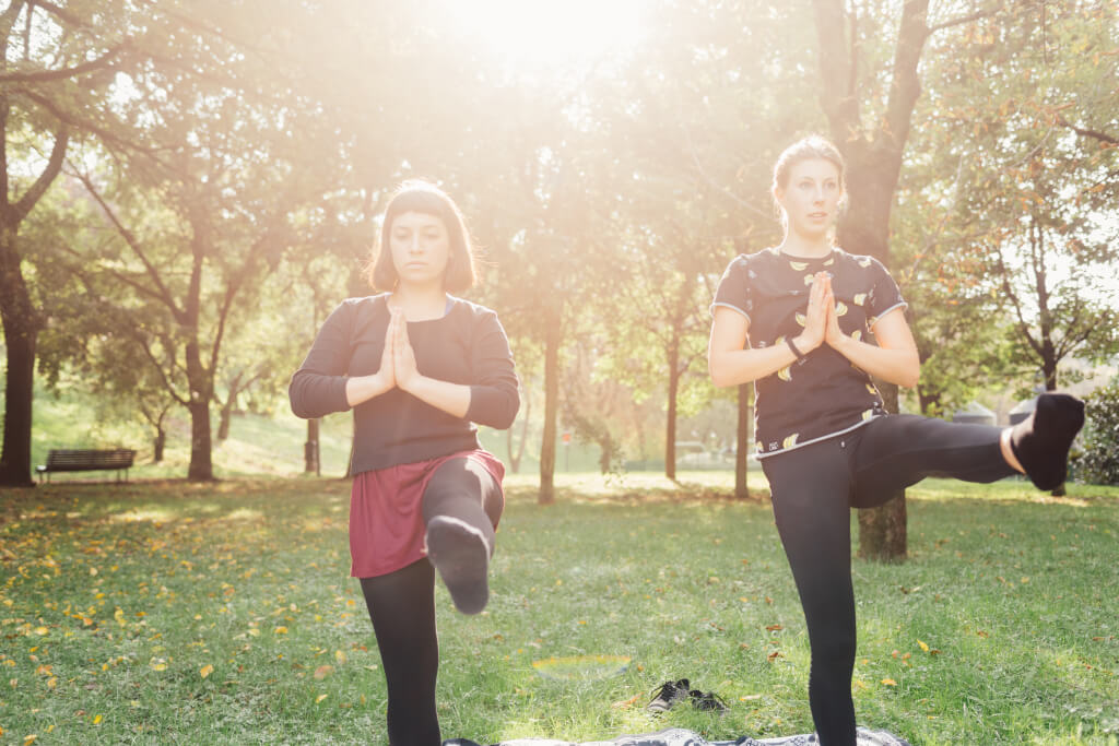 graphicstock two young beautiful caucasian women stretching outdoor in a city park in sunny day sportive training yoga concept B6XB6oYk