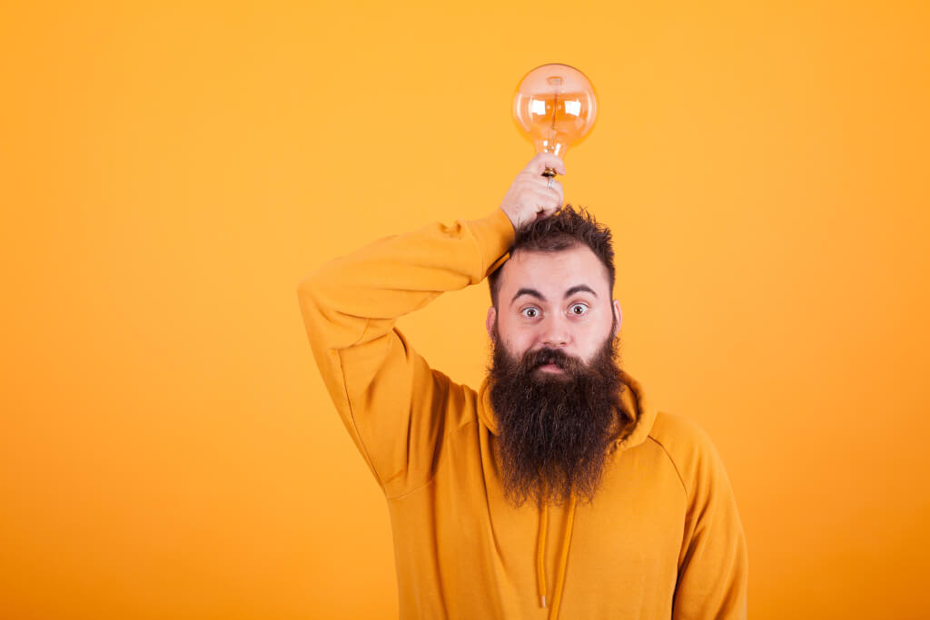 storyblocks smart bearded man holding light bulb on his head over yellow background creative mind bright idea succesful man Ss4YyMscL4