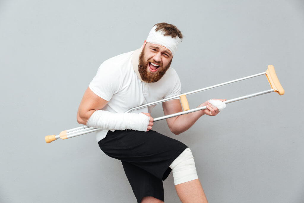 Spielerich denken cheerful playful young man having fun with crutch over white background B x0WLSBng