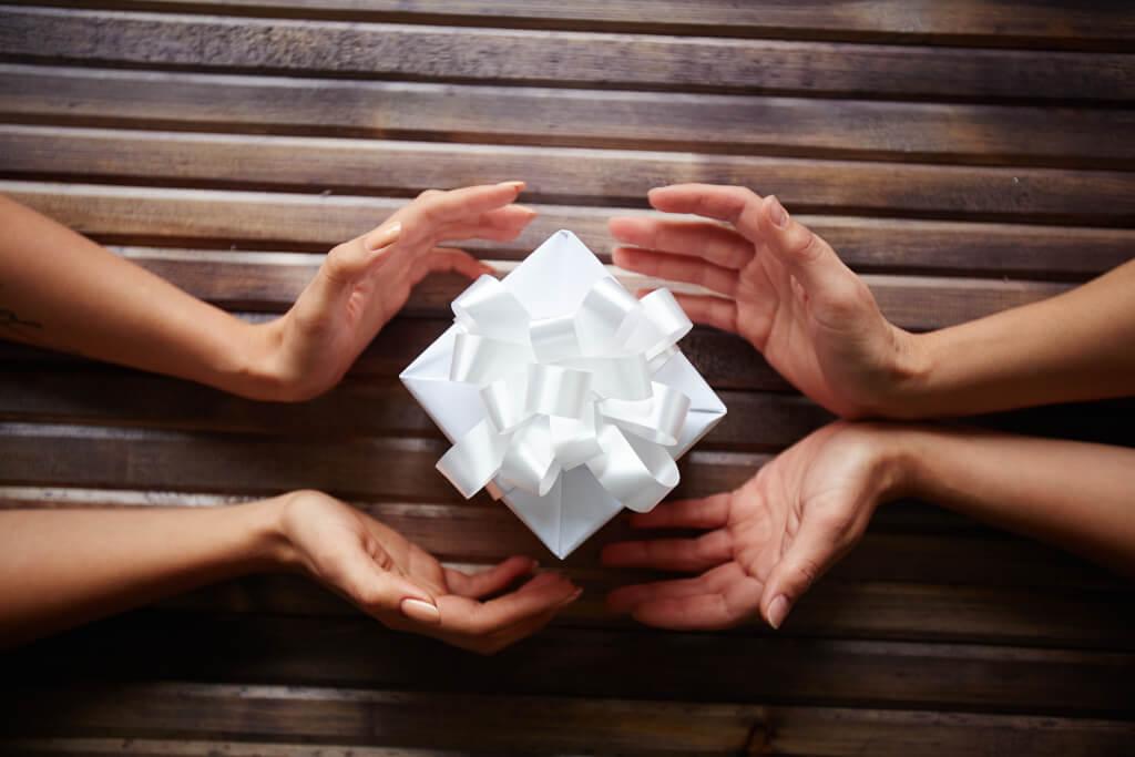 Erfülltes Leben hands surrounding a little gift box HHbUmBLolb
