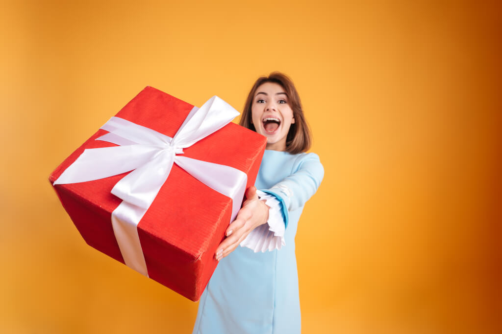 Dankbarkeit  happy excited young woman giving you gift box over yellow background B GCPuRLhe