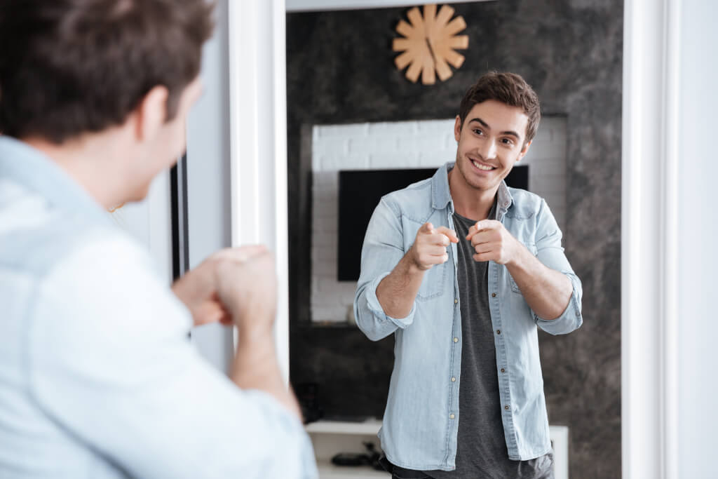Positiv verändern graphicstock smiling young man pointing fingers at his mirror reflection while standing at home B G0UO3I2g 1