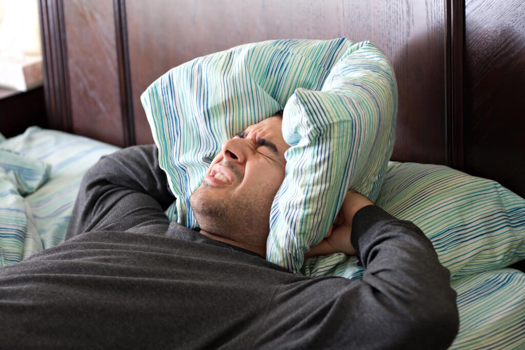 meditation zum einschlafen a man having trouble sleeping squeezes a pillow around his ears for some peace and quiet Ht0bpVdASo
