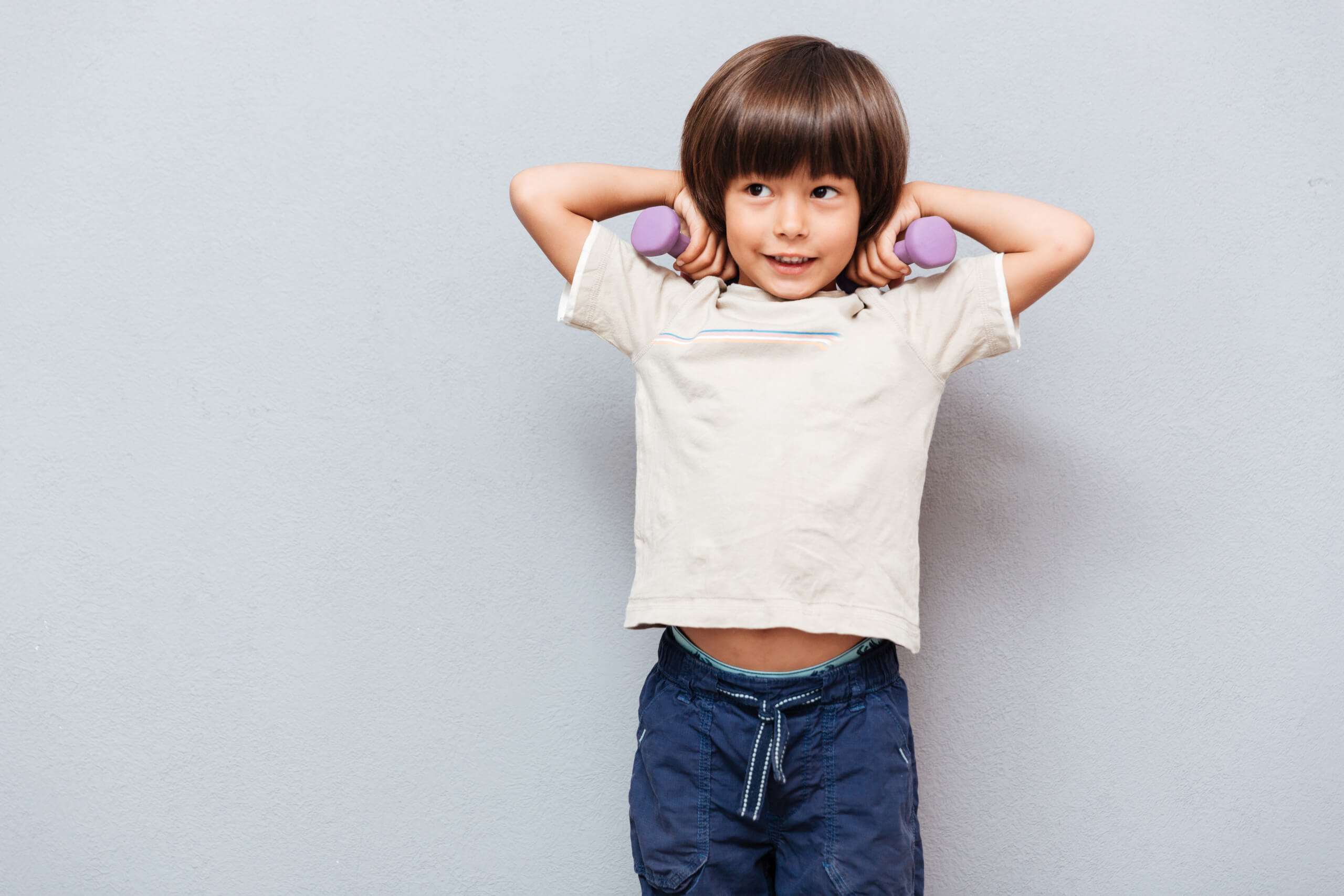 Selbstbewusstsein graphicstock happy cute little boy doing exercises with dumbbells over gray background r eMalar2e