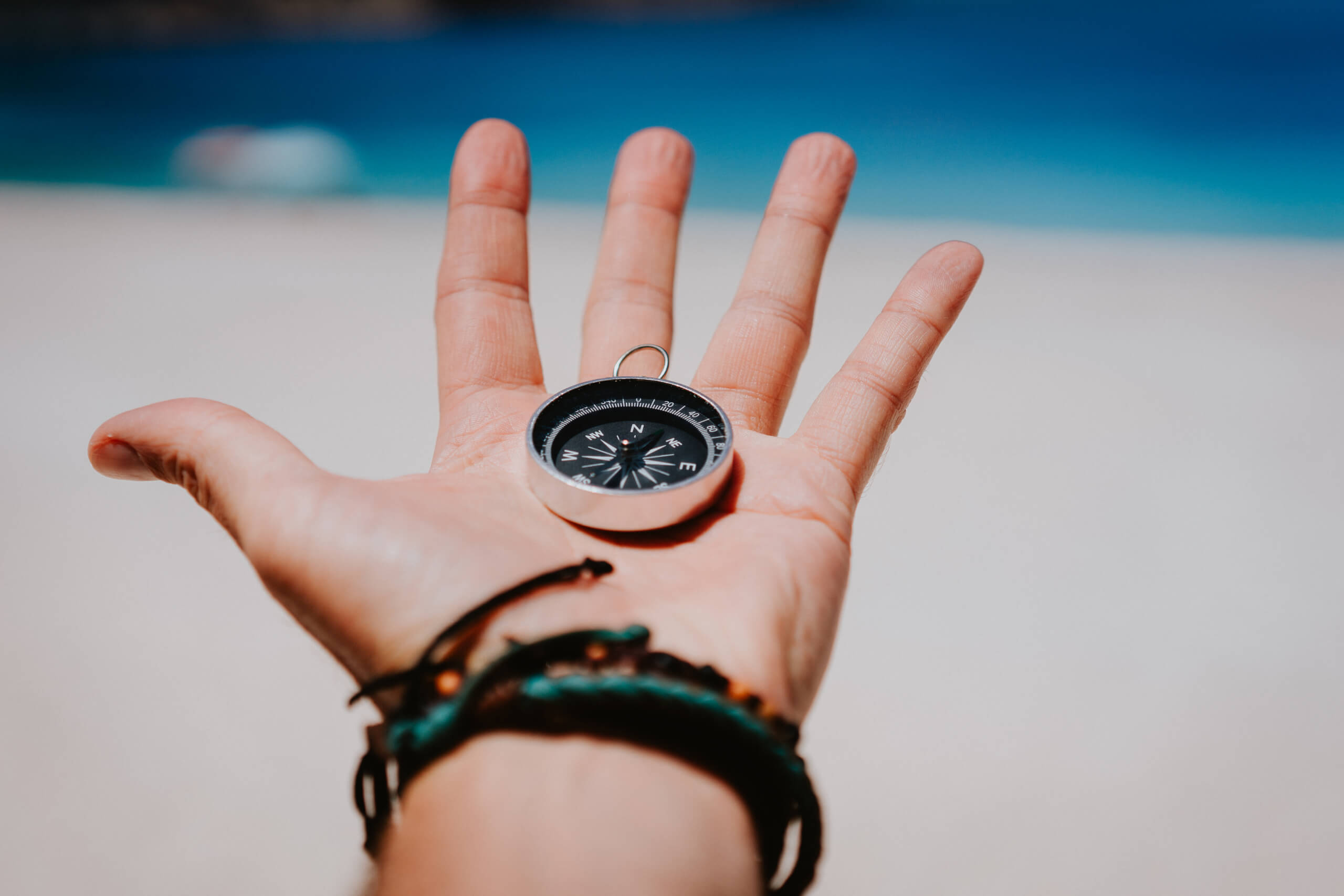 Opfer storyblocks open palm with stretched fingers holding black metal compass against white sandy beach find your way or goal concept point of view pov BeDK9JySX