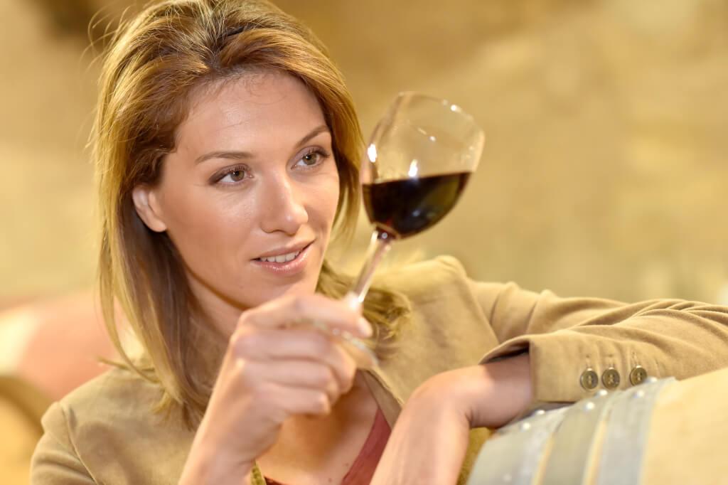Frau prueft Rotwein