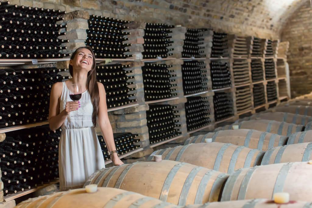 Glueckliche Frau im Weinkeller