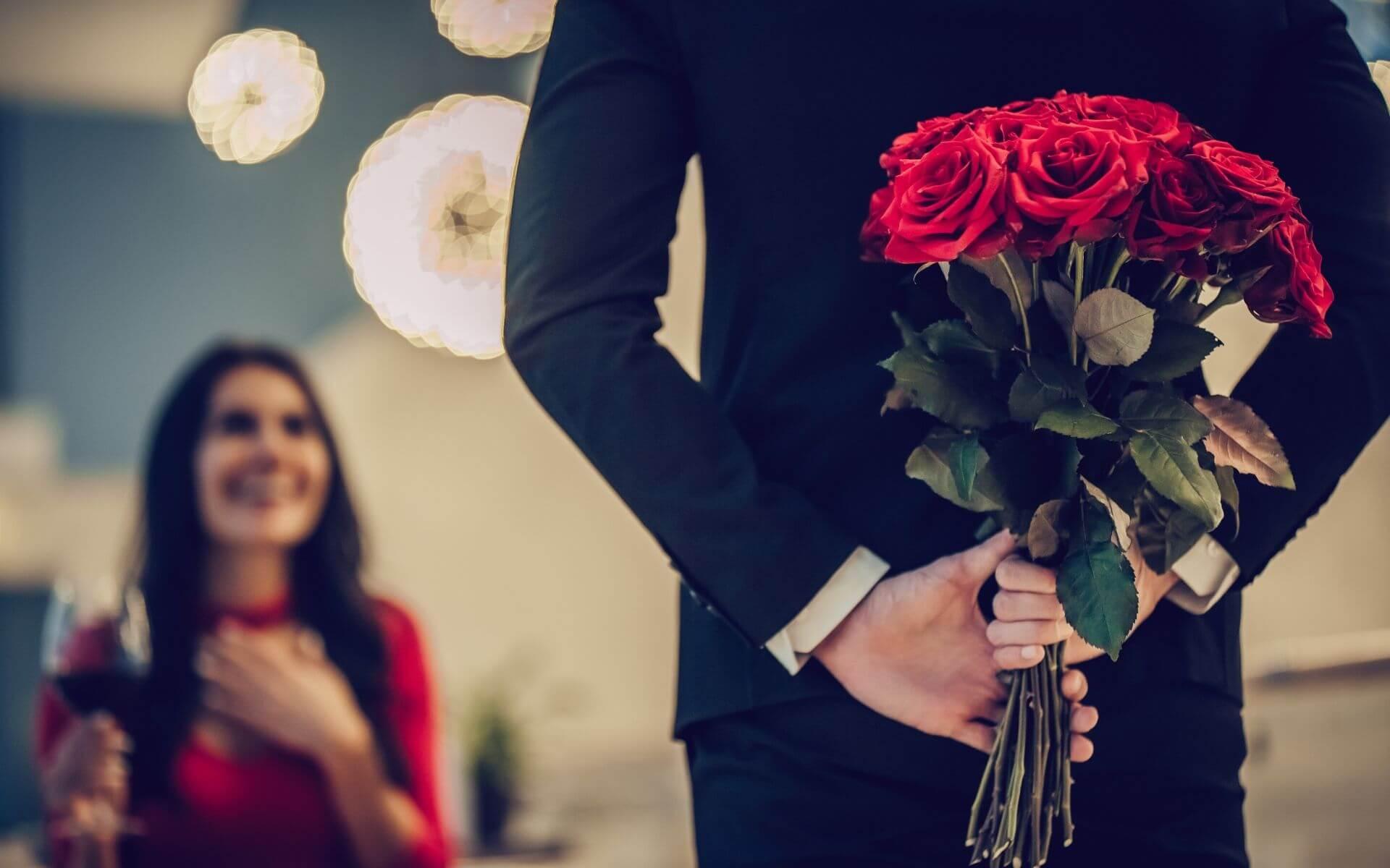Mann überrascht Frau mit Rosen