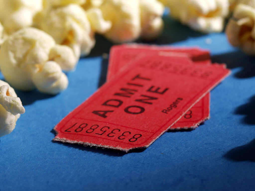 Two red cinema tickets surrounded by popcorn