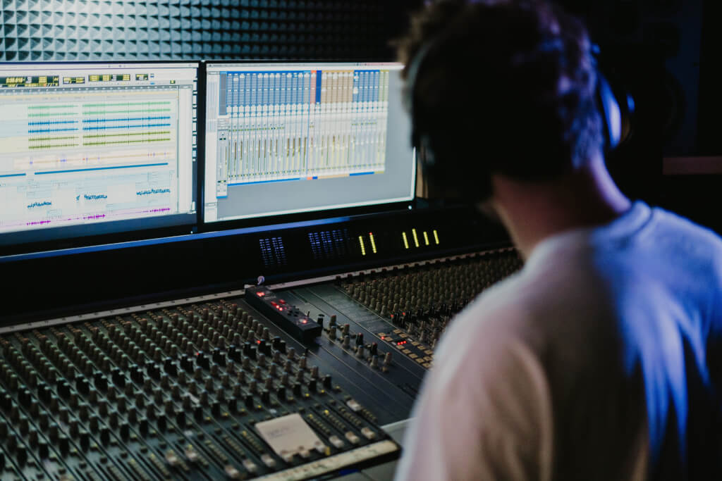 man sitting at mixing desk in recording studio
