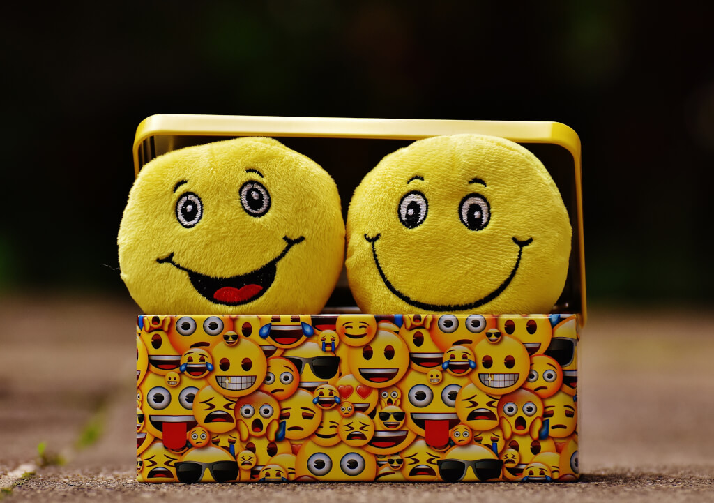 Two smiling emojis poking out from a box