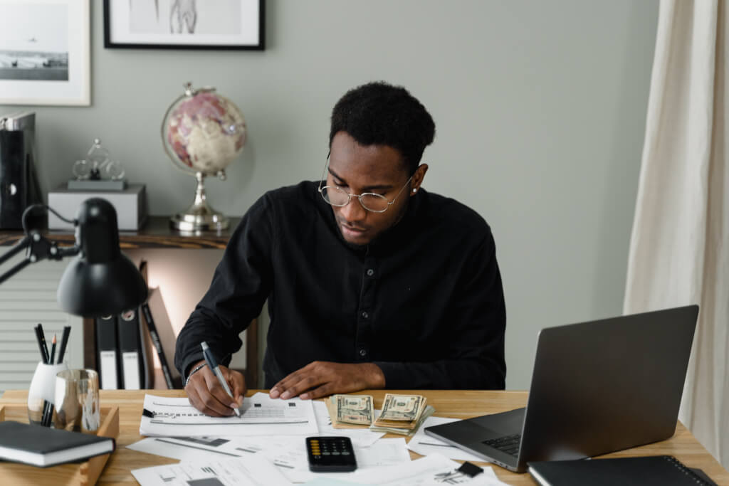 Man sitting at desk writing budget with calculator money and laptop in front of him