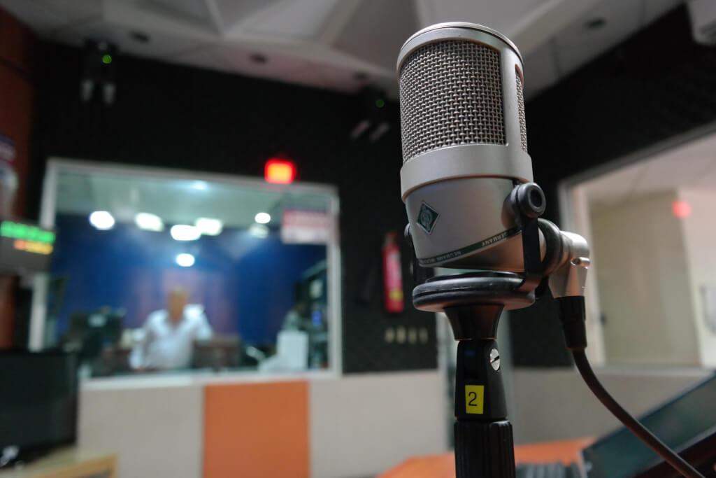 Synthetic voices: Microphone set up in a recording studio with sound engineer in the background