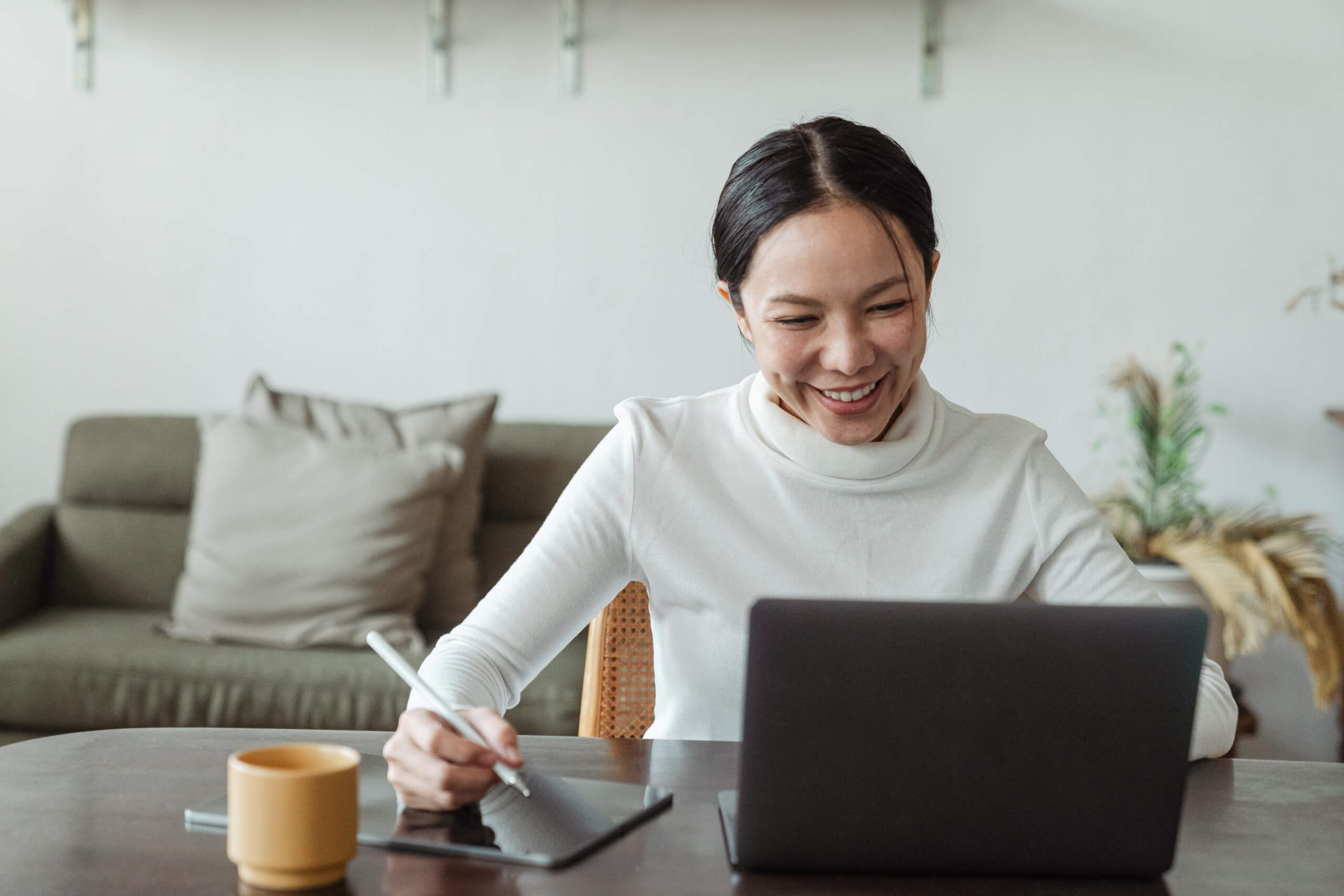 Happy woman working at home on laptop