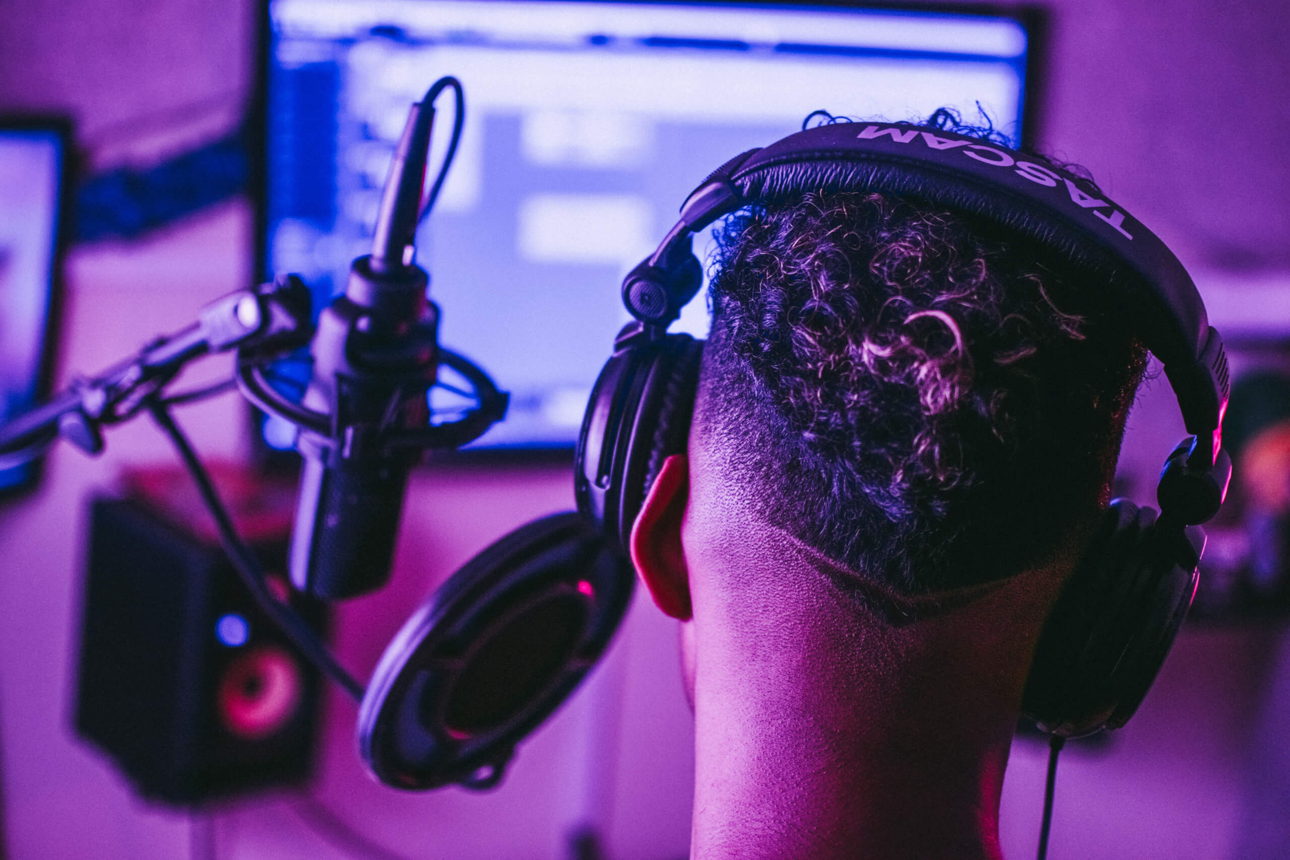 audio description software: man wearing headphones using microphone with computer in the background