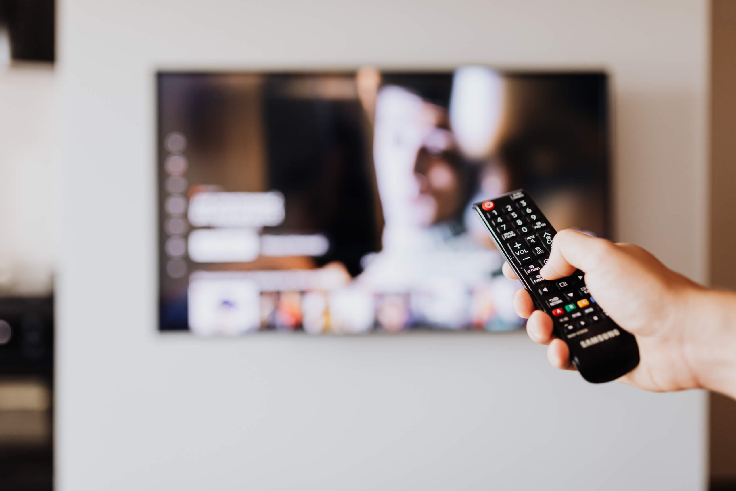 tv dialogue. A person is holding the remote control towards a television that's blurred in the background