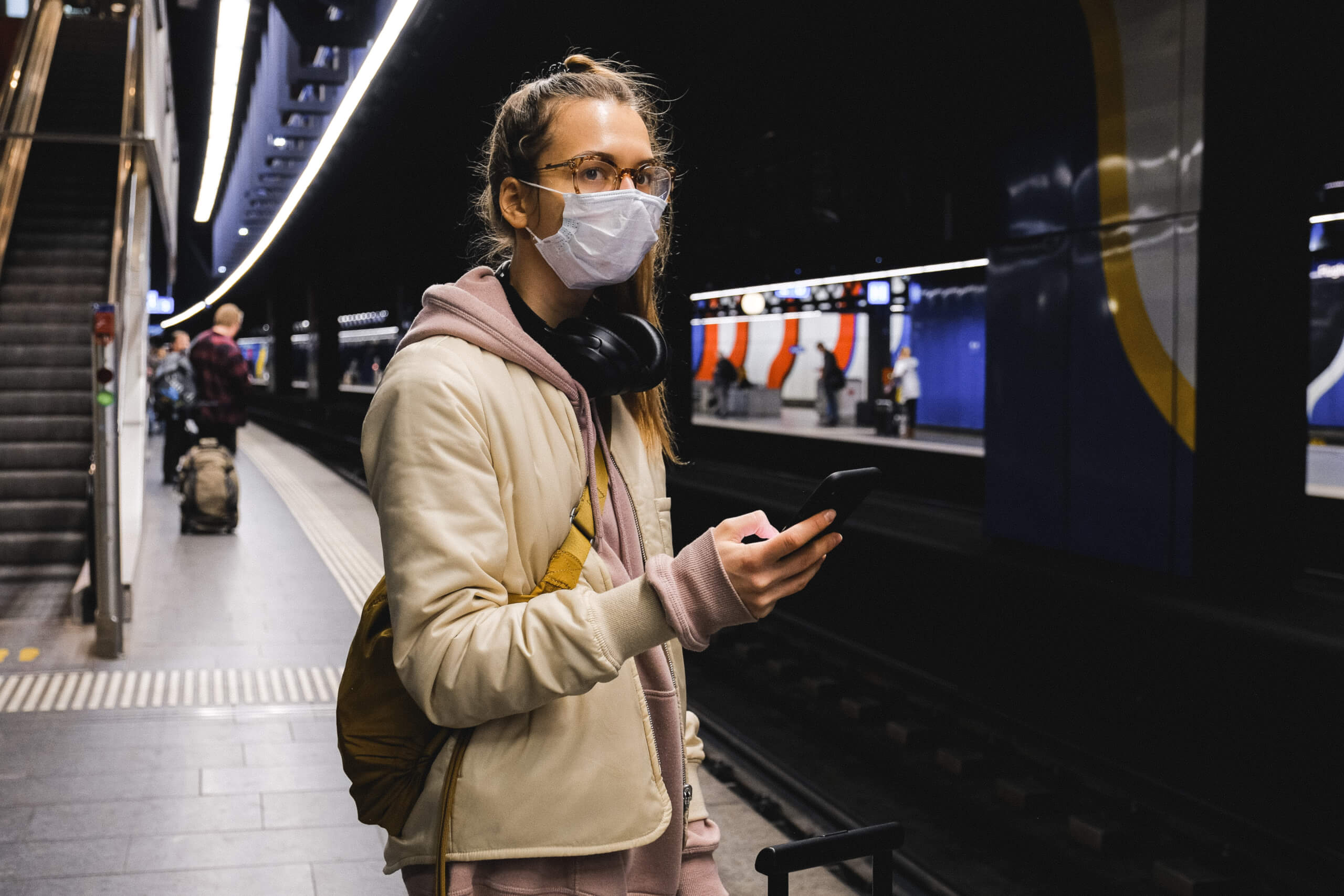 a female commuter wearing headphones and holding her phone waits for her train on the platform