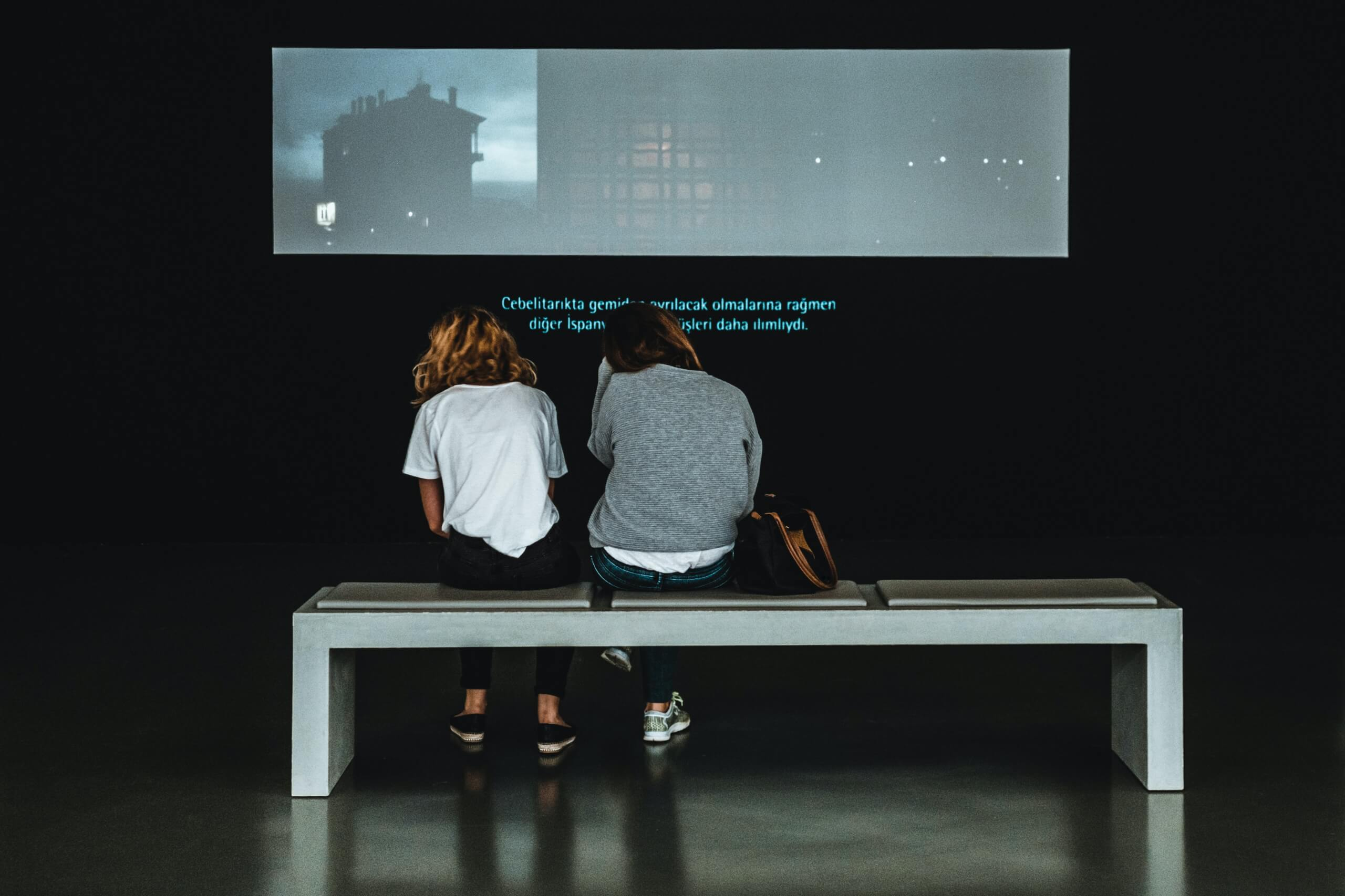 Audiovisual translation Two women watching a film at a museum with subtitles at the bottom of the screen