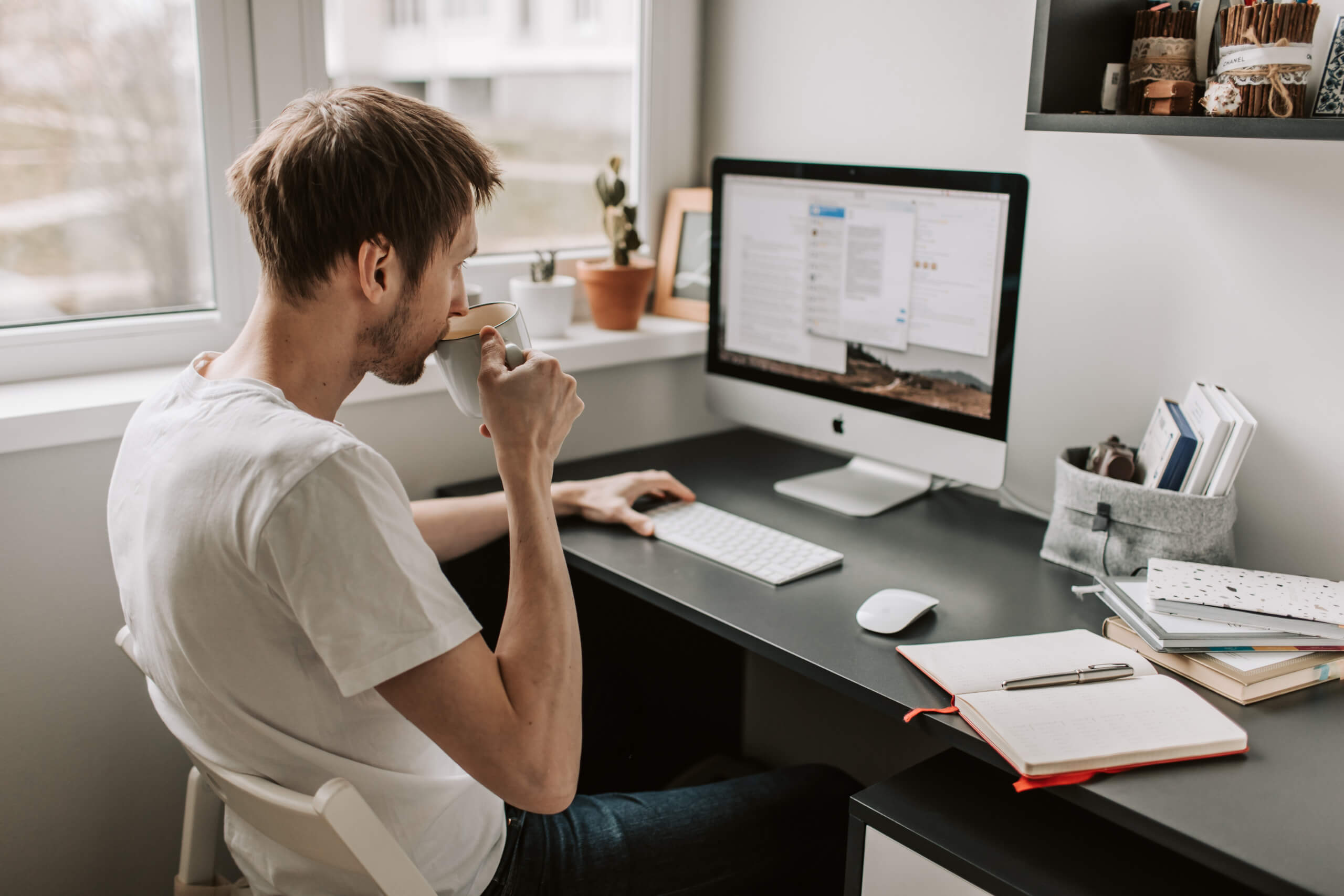Neural machine translation: a man takes a sip from a mug while doing post editing on a text on his computer
