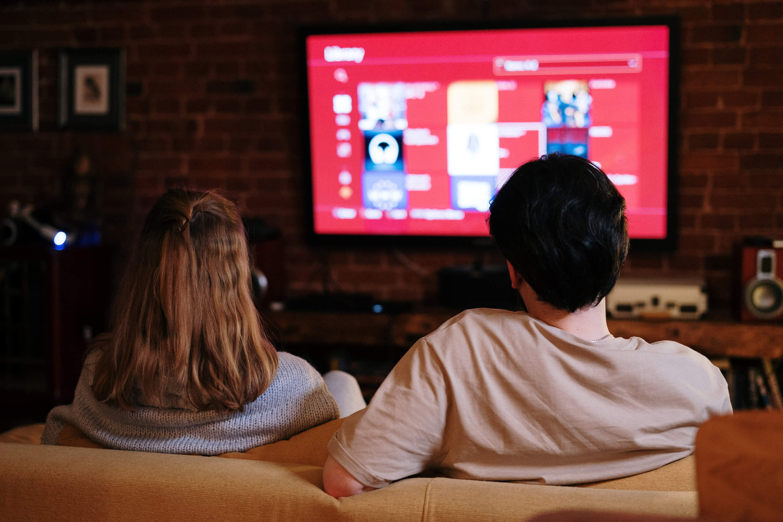 A couple sitting on the couch and browsing movies on their smart TV