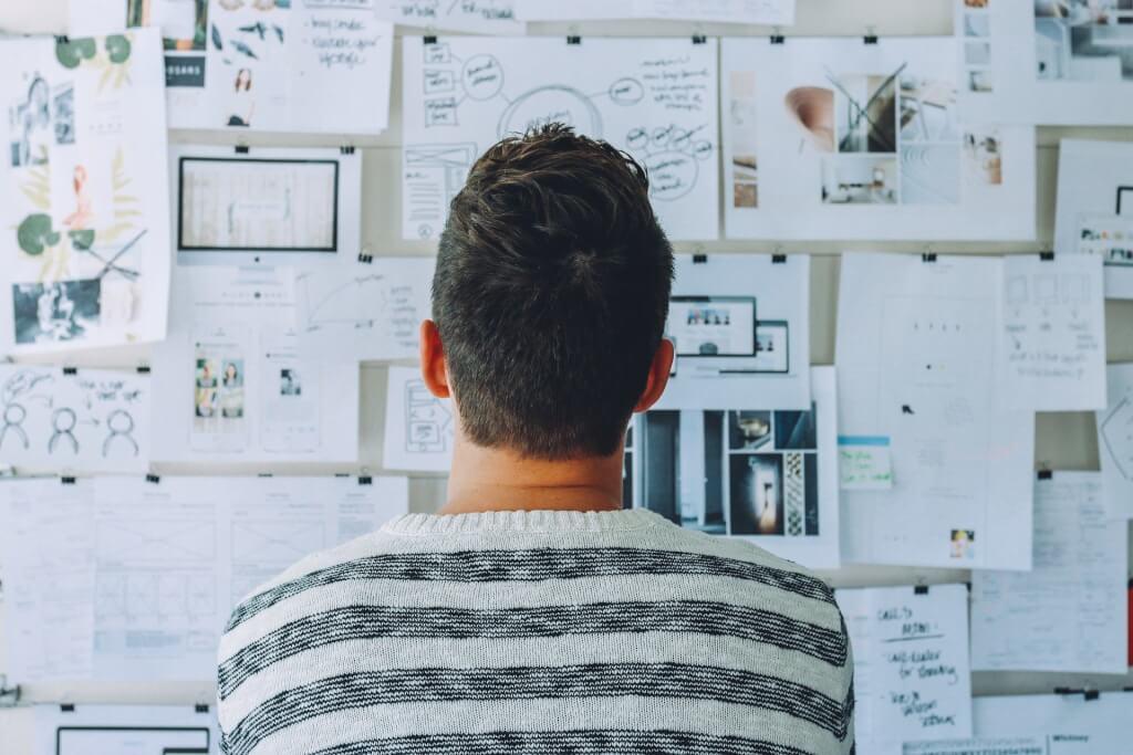 Konzepterstellung eines Mannes vor einer Wand voller Ideen auf Zetteln