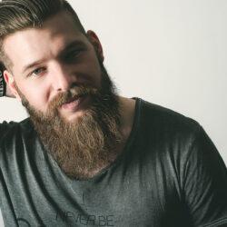 Ein männliches Model mit viel Bart hält seine rechte Hand hinter seinen Kopf und ist etwas zur Seite geneigt. Licht kommt von links.