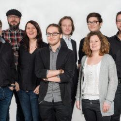 Es wurde ein ganzes Team eines Unternehmens fotografiert. Alle schauen sehr freundlich und sympathisch.