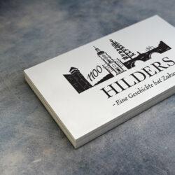 Die Marktgemeinde Hilders ist als Scherenschnitt mit deren Ruine, Zunftbaum und Kirche abgebildet.