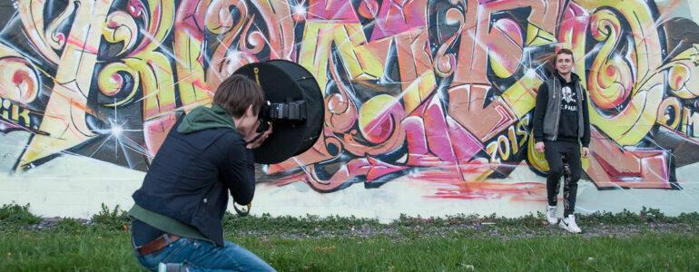 Man sieht die Fotografin Hagar Lotte Geyer auf der Wiese hockend und Ihr Model fotografieren. Das Model ist ein Jugendlicher, welcher gegen eine Graffiti-Wand steht.