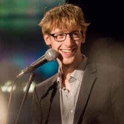 Ein junger schlanker Mann mit Brille und rot-blondem Haar steht am Mikro und schaut lachend zur Seite.