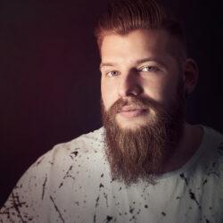 Zu sehen ist ein kräftiger Mann mit viel Bart. Die Farbigkeit des Fotos ist bräunlich gehalten, dadurch wirkt das Foto etwas weicher und wärmer, trotz des ausdrucksstarken Models.