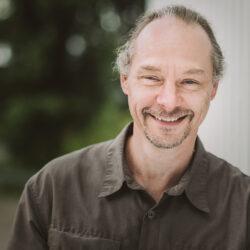 Freundlich schauender Mann lehnt mit seiner Schulter an einer Betonwand und lächelt freundlich in die Kamera. Der Hintergrund sind in die Unschärfe gezogene Bäume.