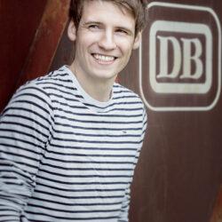 Ein junger Mann schaut lachend an der Kamera vorbei. Er steht vor einer rostigen Wand und ist mit einem gestreiften langärmligen T-Shirt bekleidet.