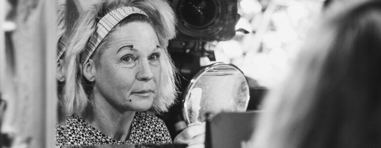 Clownfrau Gaya schminkt sich gerade uns chaut freundlich in den Spiegel. Eine Kamerad Frau vom hr-Fernsehn filmt sie dabei.