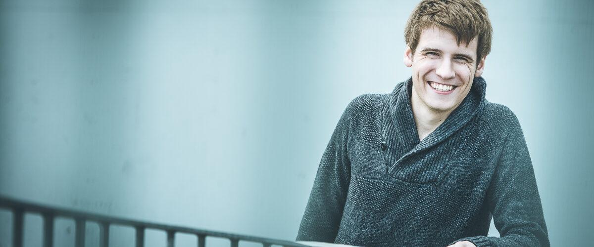 Ein junger, sympathischer, gutzusehender Mann lehnt an einem Geländer. Hinter ihm ist eine Betonmauer. Er lacht freundlich in die Kamera. Der Bildlook ist sehr kontrastreich und farblich grün/blau gehalten.