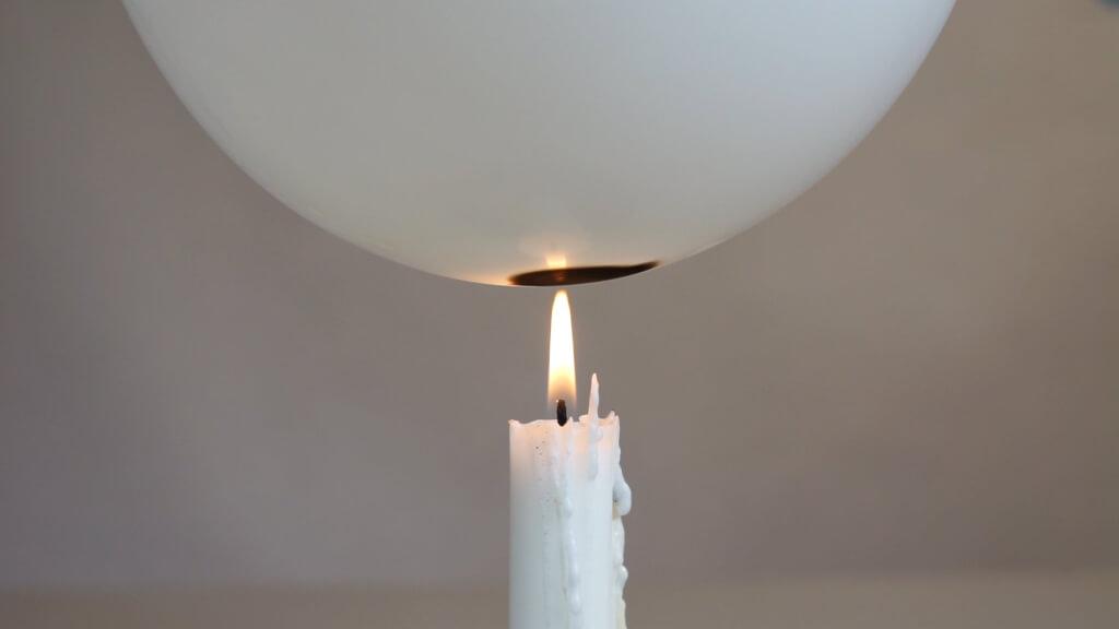 Wenn Wasser im Luftballon ist, kann man eine Kerzenflamme an die Ballonhalt halten, ohne dass der Ballon platzt