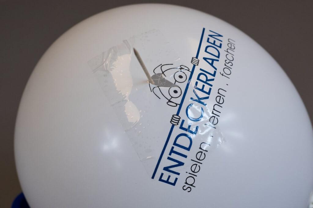 Ein Klebestreifen verhindert, dass der Luftballon platzt, wenn man hineinsticht