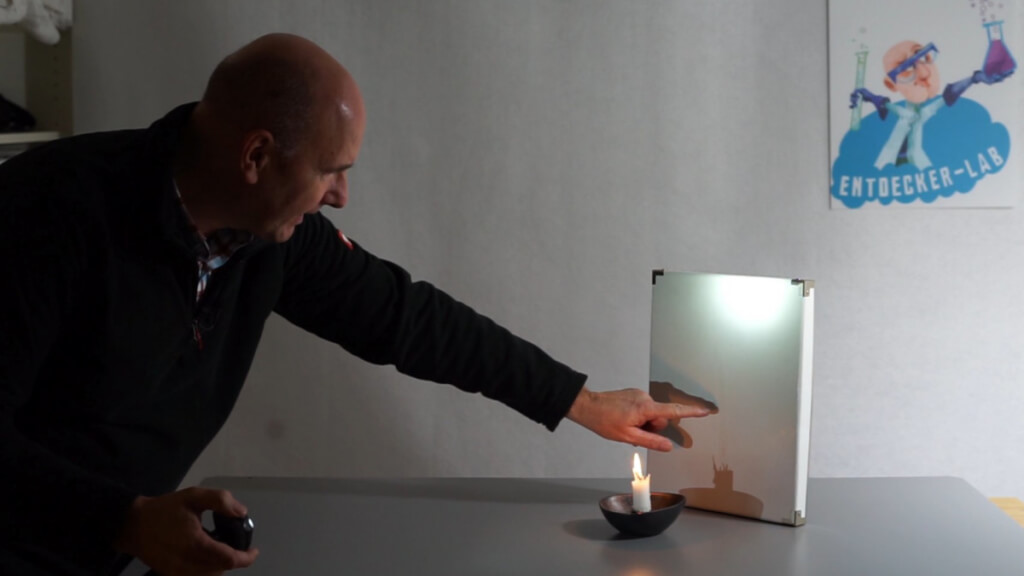Im Kerzenschatten Experiment wird die  Flamme mit Taschenlampe durchleuchtet