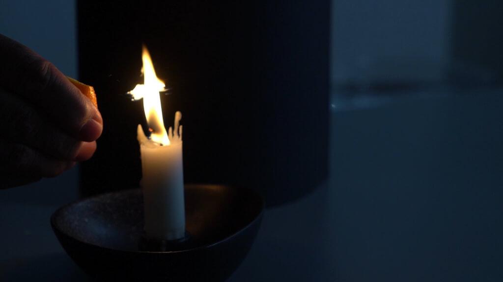Orangenschalen knicken. Öl spritzt in die Kerzenflamme und verbrennt.
