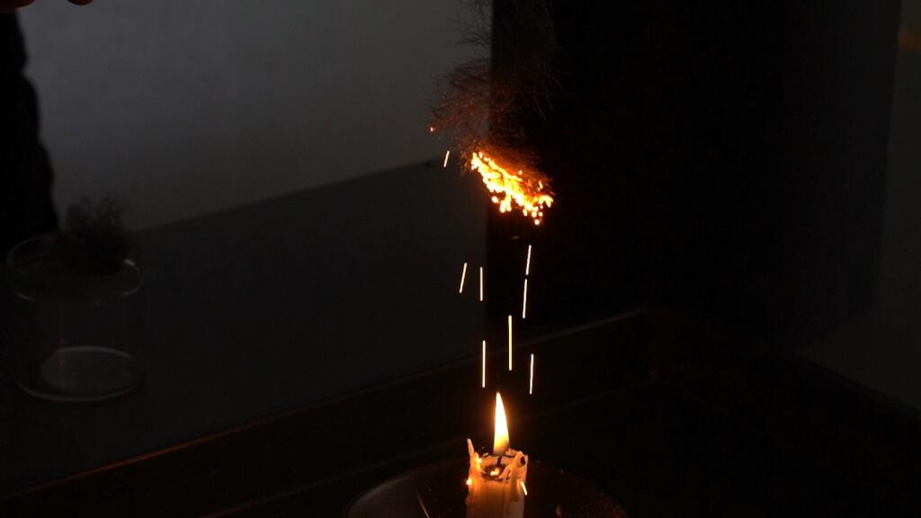 Eisenwolle brennt in einer Kerzenflamme.