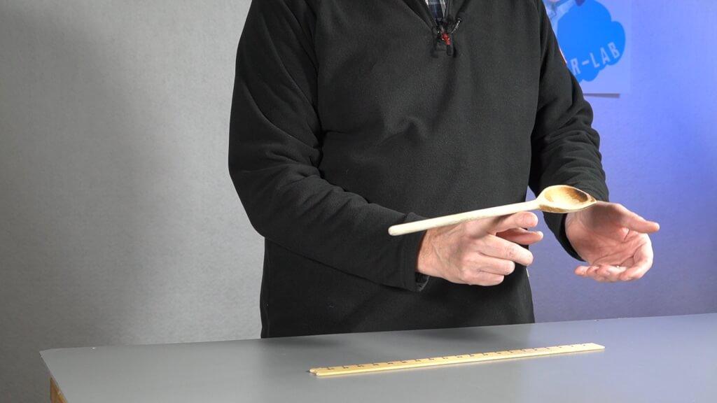 Der Kochlöffel ist an einer Seite schwerer. Der Schwerpunkt verschiebt sich zu dieser Seite.