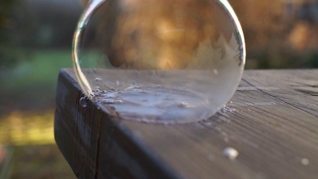 Die Seifenblase beginnt einzufrieren. Eiskristalle wachsen von unten nach oben.