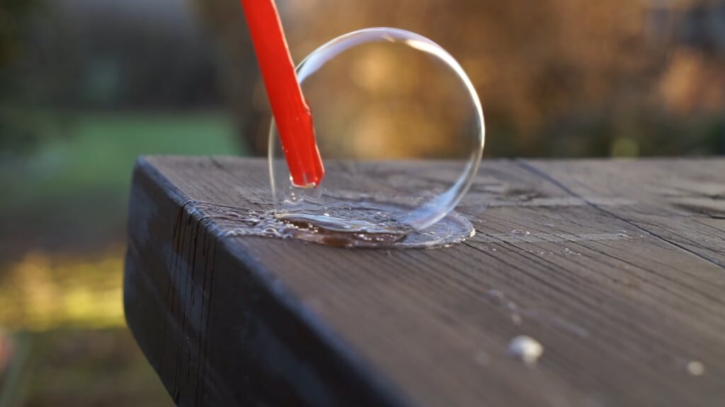 Wir pusten die Seifenblase mit einem Trinkhalm auf an einer Stelle, die wir vorher mit Seifenblasenlösung angefeuchtet haben.