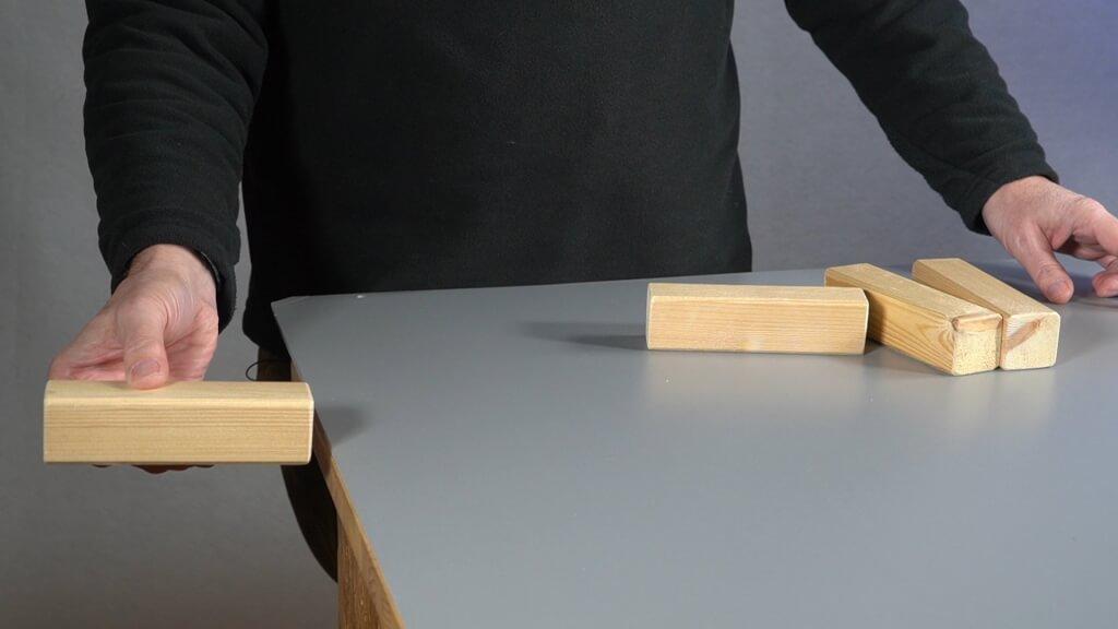 Ein Baustein soll komplett längs über der Tischkante hängen