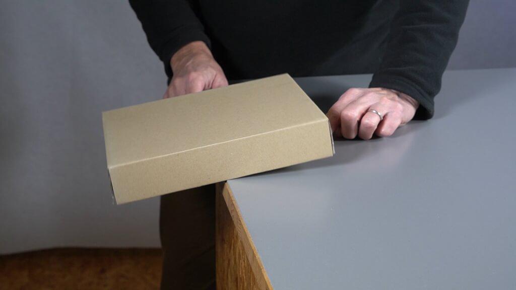 Kurz bevor die Schachtel fällt, verhält sich die Schachtel wie eine Wippe.
