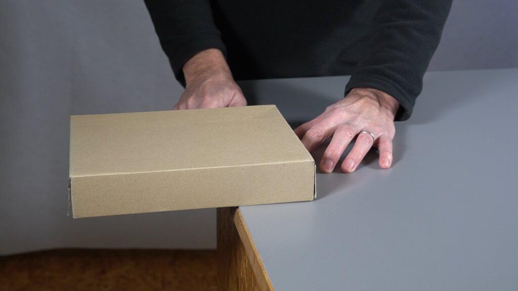Der Schwerpunkt der Schachtel liegt jetzt weiter rechts. Ihr könnt sie viel weiter über die Tischkante schieben.