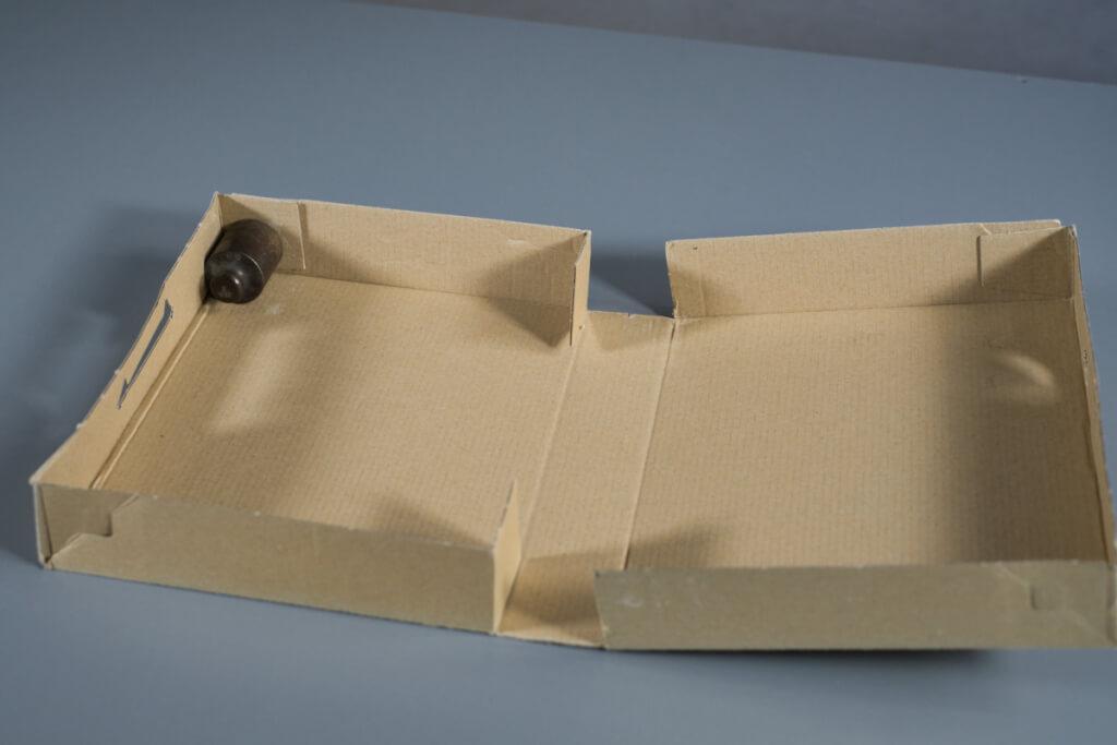 Klebt ein Gewicht mit Klebeband oder Heißkleber in die Ecke der Schachtel.