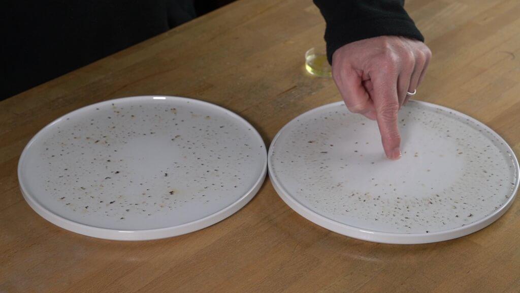 Der Finger mit dem Spielmittel sorgt dafür, dass die Pfefferkörner zum Rand des Tellers gedrängt werden.