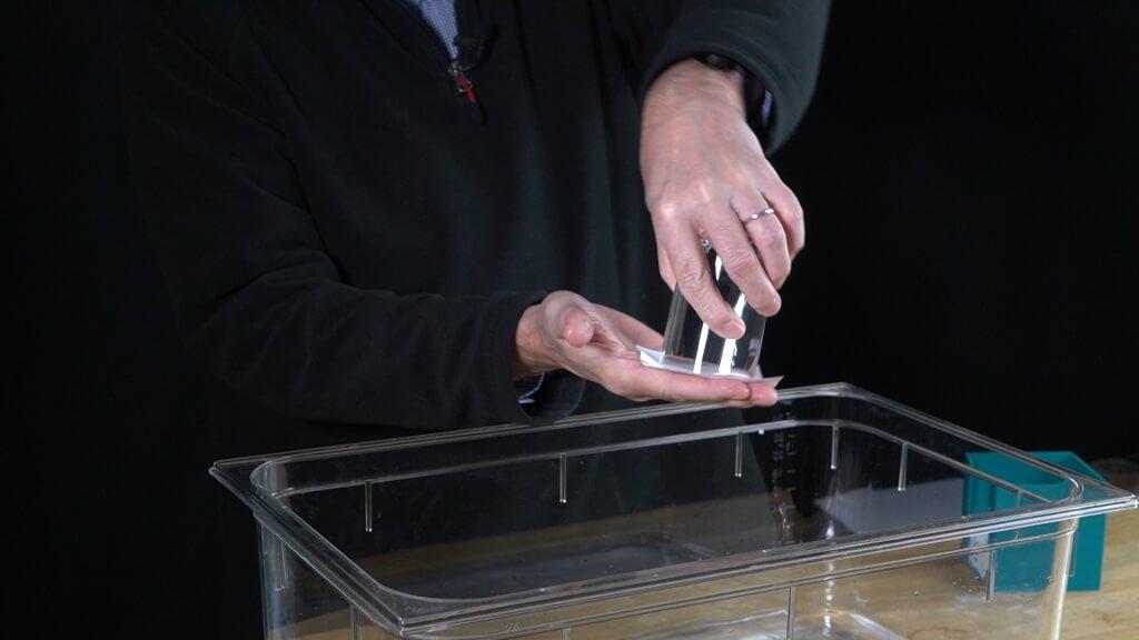 Das Wasserglas wird mit einem Blatt Papier abgedichtet.