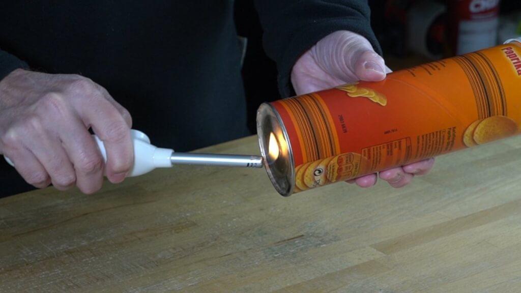 Das Benzin in der Chipspackung ist verdampft und wird über das Loch im Boden der Packung entzündet.